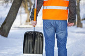Man with a snow shovel on the sidewalk in winter — Stockfoto