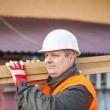 Carpenter with boards on their shoulders — Stock Photo