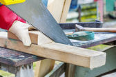 Carpenter sawing plank on to the work table at outdoor — Stock Photo