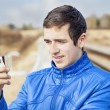Teen with cell phone on the railway — Stock Photo #45761821