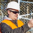 Engineer with the cell phone near to the fence — Stock Photo #45761855