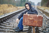 Teenage boy with a suitcase on the railway in rain — Stock Photo