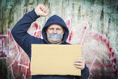 Demonstrator with a tape on a mouth and poster near to the wall — Stock Photo