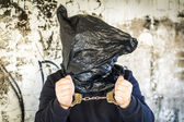 Hostage in handcuffs and with a bag on head — Stockfoto