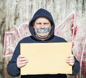 Demonstrator with a tape on a mouth and poster in hands — Stock Photo