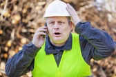 Surprised worker with cell phone — Stock Photo