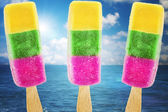 Ice cream in three colors on summer sea background — Stock Photo