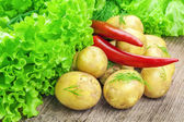 Fresh potatoes with lettuce and peppers on table — Stock Photo