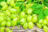 Green grapes with leaves on a old wooden board — Stock Photo