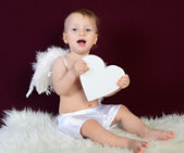 Kid dressed as an angel sitting on a red background — Stock Photo