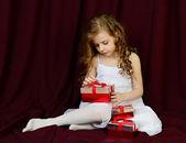 Beautiful girl sitting on a red background with gifts — Stock Photo