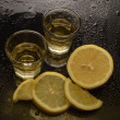 Tequilas with lemons on black background - Stock Photo