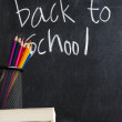Books and colorful pencils with hand writing Back To School on chalkboard — Foto Stock