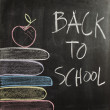 Hand writing Back To School with hand drawn colorful books and apple on chalkboard — Stock Photo
