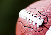 Close up of an american football against a black background — Stok fotoğraf