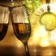 Glasses with champagne against fireworks - Stock Photo