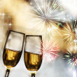 Glasses with champagne against fireworks — Stock Photo #17612905