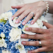 Hands and rings on wedding bouquet — Stock Photo #26312717