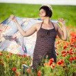 Young pregnant woman in poppy field — Stock Photo