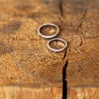 Wedding rings on wooden background — Stock Photo #28618287