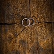 Wedding rings on wooden background — Stock Photo #28747413