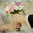Hands and rings on wedding bouquet — Stock Photo #29129495