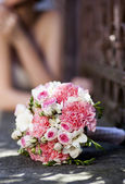 Beautiful white and pink wedding bouquet with bride in the background — Stock Photo
