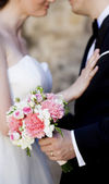 Bride and groom hands holding wedding bouquet — Stock Photo