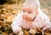 Baby girl on autumn leaves — Stock Photo
