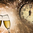Champagne glasses, clock and fireworks at midnight — Stock Photo