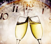 Glasses with champagne and clock close to midnight — Stock Photo
