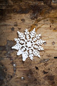 Snowflake on old wooden background — Stock Photo