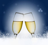 Glasses with champagne against blue background and snowflakes — Stock Photo