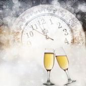 Glasses with champagne against fireworks and clock close to midnight — Stock Photo