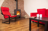 Home interior with fireplace, red book and tea on table — Stock Photo