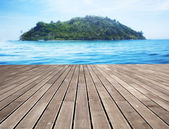 Wooden pier and distant island — Stock Photo