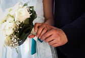Hands and rings on wedding bouquet — Стоковое фото