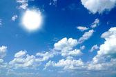 Blue sky with Altocumulus castellanus cloud and sun closeup — Stock Photo