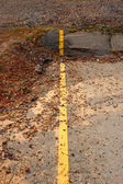 Yellow line on the road cracks and disintegrates. — Stock Photo