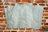 Wrinkled old paper on the brick. — Stock Photo