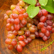 Foto Stock: Fresh red grapes on brown wood.