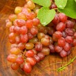 Fresh red grapes on brown wood. — Stock Photo #34427889