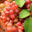 图库照片: Fresh red grapes on brown wood.