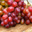 Fresh red grapes on brown wood. — Stockfoto #34475351