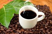 Caffè e chicchi di caffè su sfondo legno — Foto Stock