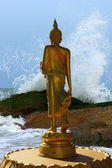 Buddha statues was walking on the beach and wave — Photo