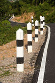 Stone pillars prevent accidents on the road curved. — Stock Photo