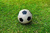 Old soccer ball on green grass — Stock Photo