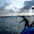 Silhouettes fisherman casting on a crab boat. — Stock Photo