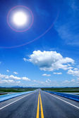Empty road and the yellow traffic lines with blue sky. — Stock Photo